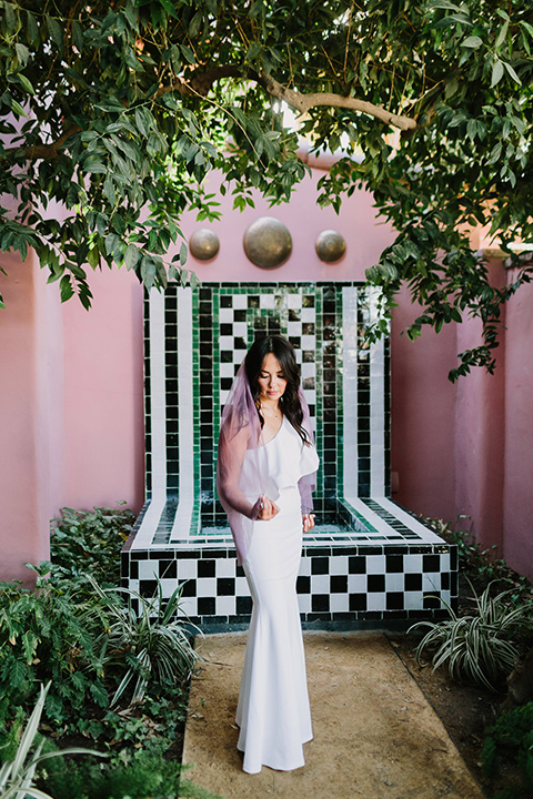 bride in a white bohemian gown with one sleeve and a ruffled detail