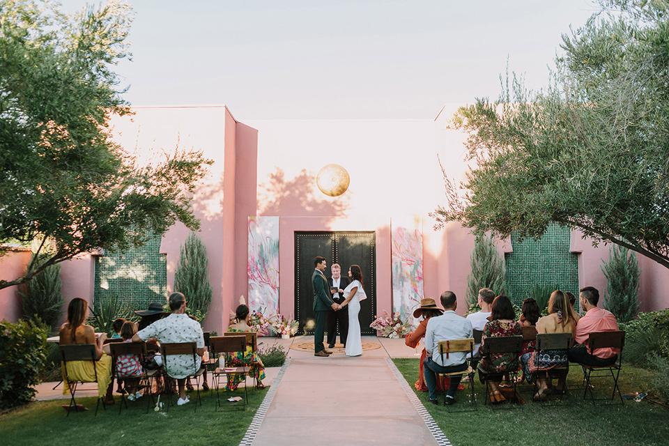 bride in a white bohemian gown with one sleeve and a ruffled detail with a pink veil and the groom in a green suit with a white shirt, bolo tie, and wide brimmed hat at the ceremony