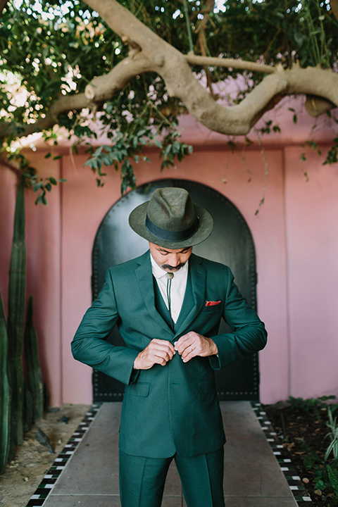 the groom in a green suit with a white shirt and bolo tie and wide brimmed hat buttoning his jacket