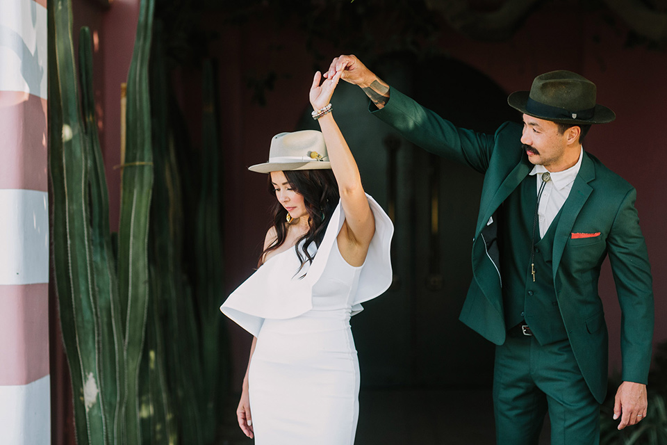 bride in a white bohemian gown with one sleeve and a ruffled detail with a pink veil and the groom in a green suit with a white shirt, bolo tie, and wide brimmed hat dancing