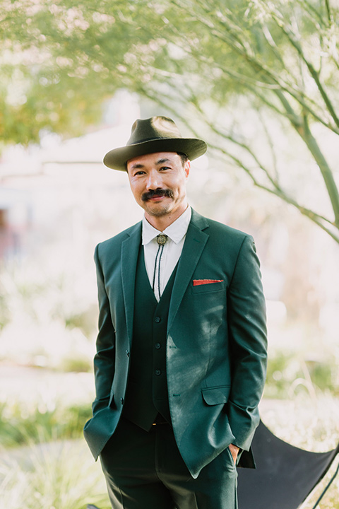 the groom in a green suit with a white shirt, bolo tie, and wide brimmed hat smiling at the camera