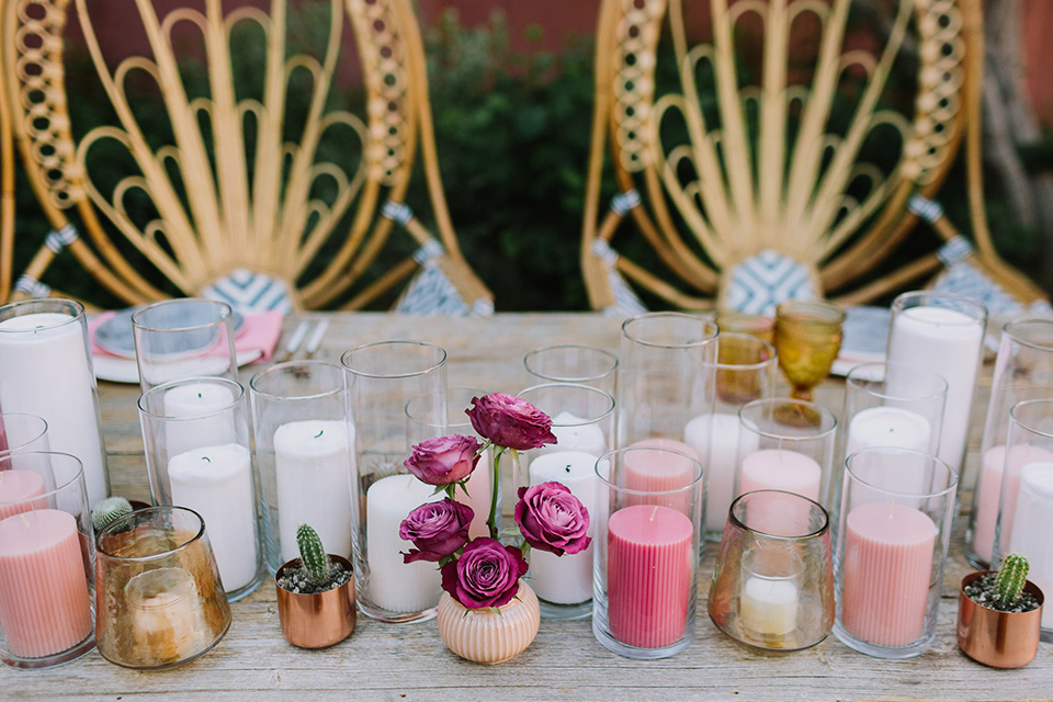 wooden bohemian chairs at the sweetheart table with short and tall candles in many different fun colors