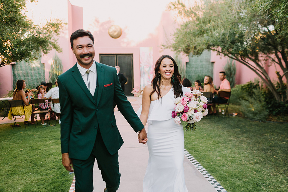 bride in a white bohemian gown with one sleeve and a ruffled detail with a pink veil and the groom in a green suit with a white shirt, bolo tie, and wide brimmed hat walking down the aisle