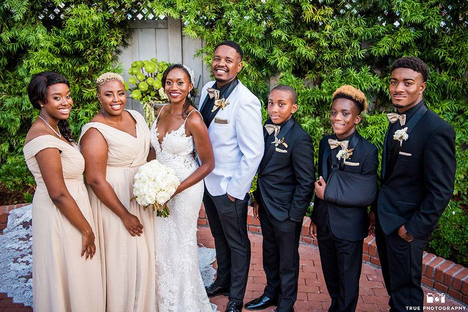 bride in a white formfitting gown with a plunging neckline and lace detailing and the groom in a white shawl lapel tuxedo with a black shirt and gold bow tie, the bridesmaids in a gold long gowns and the groomsmen in all black tuxedos and gold bow ties