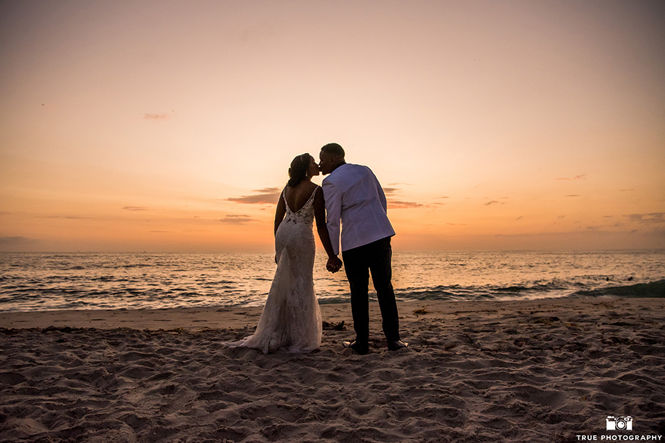 bride in a white formfitting gown with a plunging neckline and lace detailing and the groom in a white shawl lapel tuxedo with a black shirt and gold bow tie, at sunset
