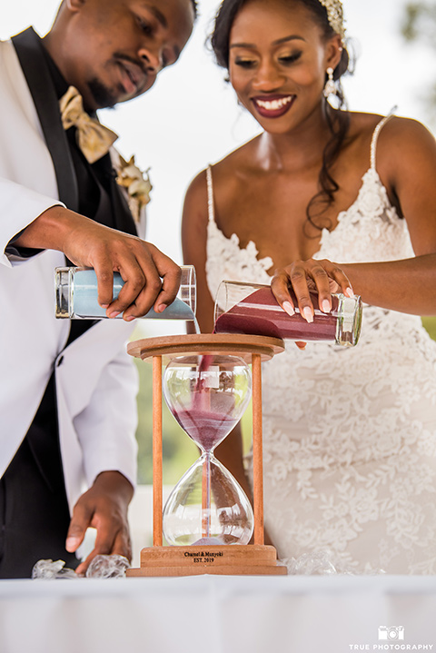 bride in a white formfitting gown with a plunging neckline and lace detailing and the groom in a white lace tuxedo with a black shirt and gold bow tie, with sand at ceremony