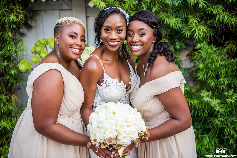 bride in a white formfitting gown with a plunging neckline and the bridesmaids in gold long gowns
