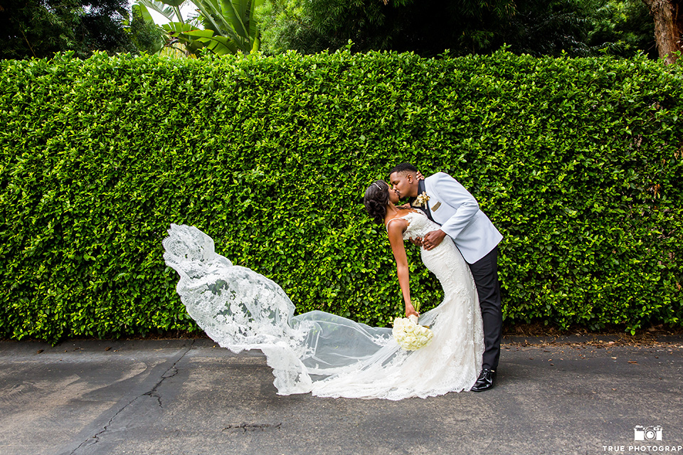 bride in a white formfitting gown with a plunging neckline and lace detailing and the groom in a white shawl lapel tuxedo with a black shirt and gold bow tie, kissing by ivy wall