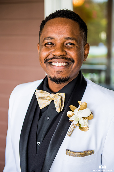 the groom in a white lace tuxedo with a black shirt and gold bow tie, smiling at the camera