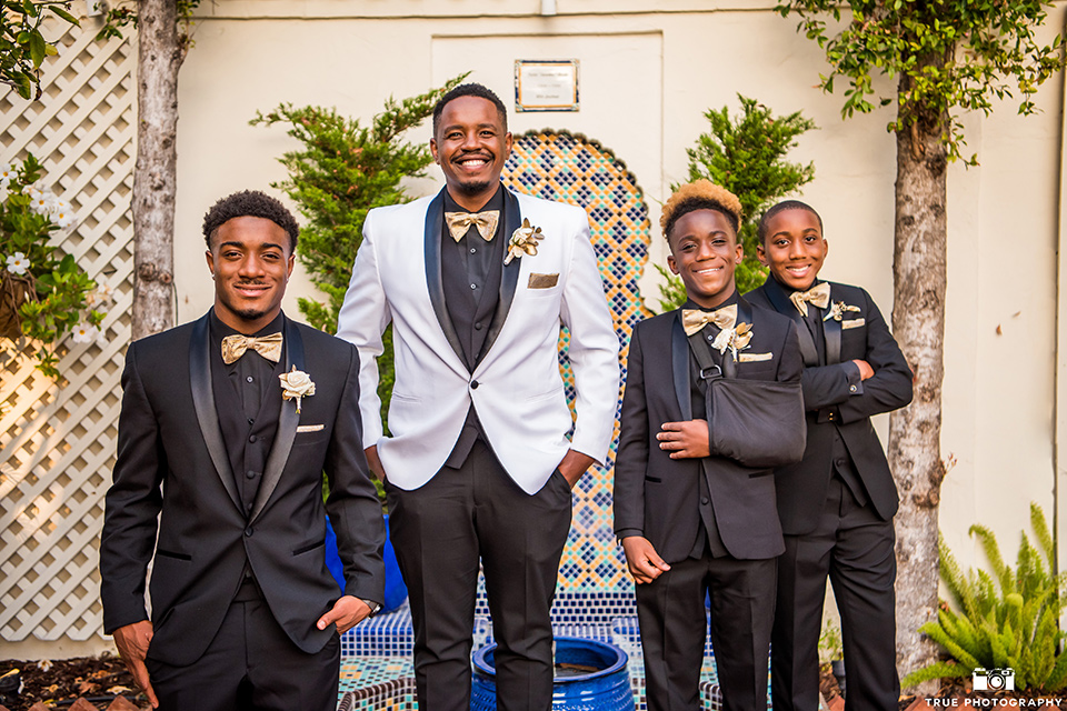 the groom in a white shawl lapel tuxedo with a black shirt and gold bow tie and groomsmen in all black tuxedos with gold bow ties