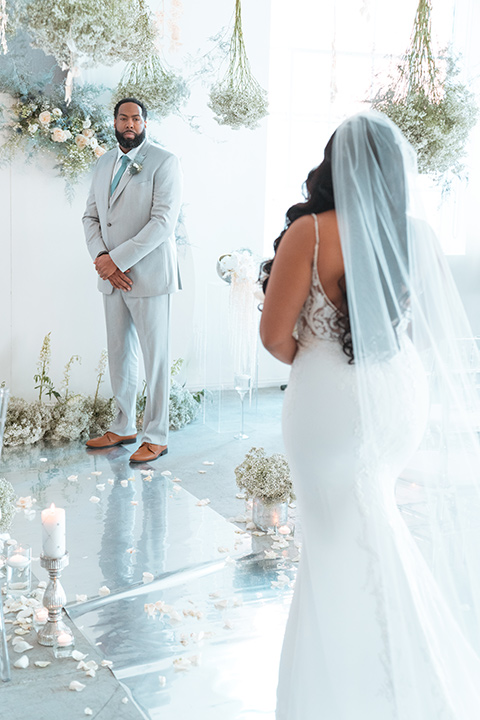 bride in a formfitting satin gown and a cathedral length veil and the groom in a light grey peak lapel suit with a teal blue bow tie