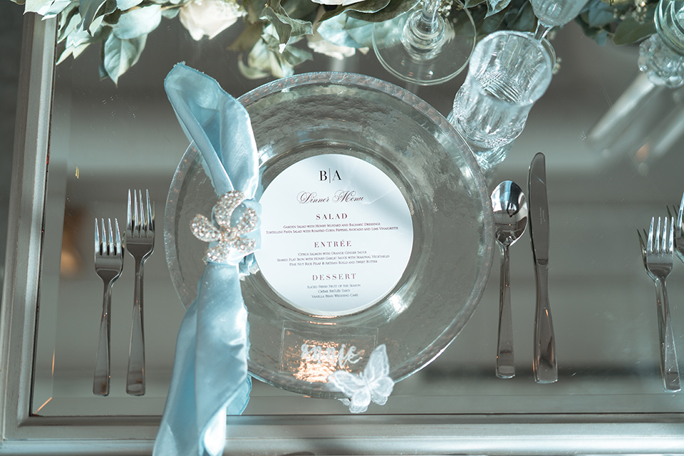 glass table with blue and silver flatware