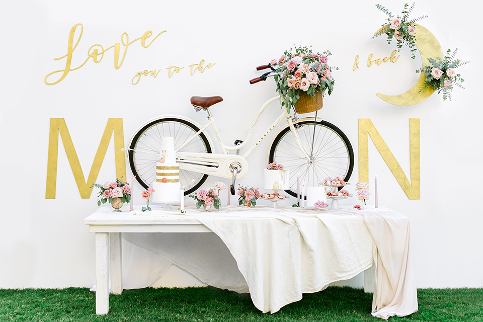 venue with a painting that says over the moon, with a white table with deserts