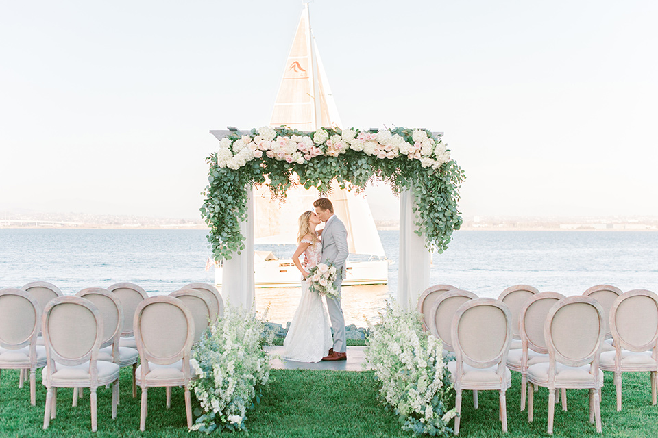 bride in a white formfitting lace gown with an off the shoulder detailing and her hair in loose waves, the groom in a light grey suit with a white long tie at the ceremony space