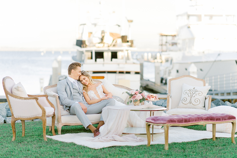 bride in a white formfitting lace gown with an off the shoulder detailing and her hair in loose waves, the groom in a light grey suit with a white long tie sitting at their reception space together with white vintage furniture and wooden tables