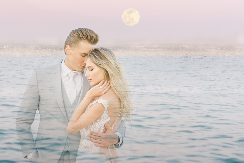 bride in a white formfitting lace gown with an off the shoulder detailing and her hair in loose waves, the groom in a light grey suit with a white long tie near the ocean