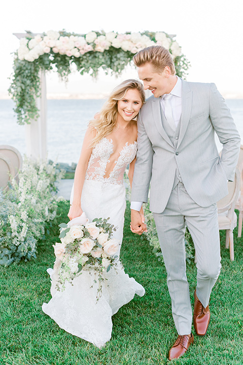 bride in a white formfitting lace gown with an off the shoulder detailing and her hair in loose waves, the groom in a light grey suit with a white long tie walking down the aisle
