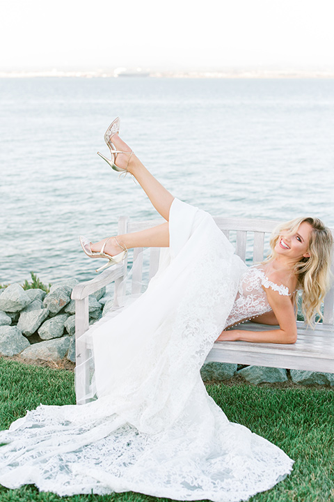 bride in a white formfitting lace gown with an off the shoulder detailing and her hair in loose waves