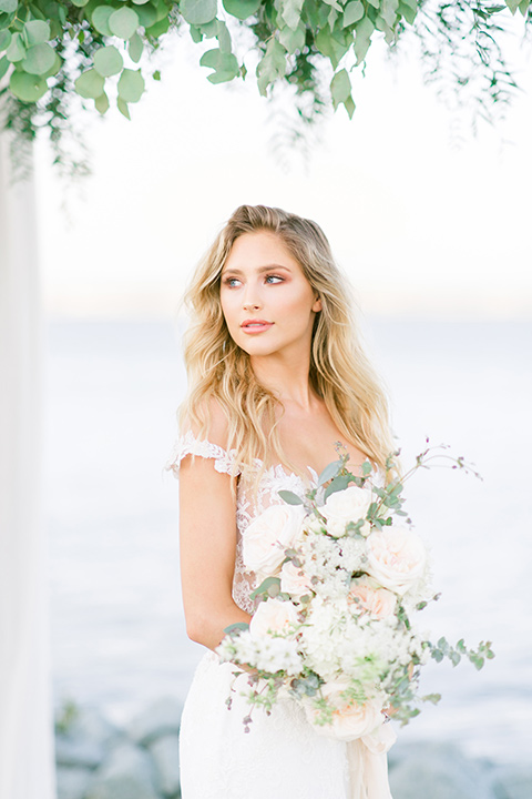 bride in a white formfitting lace gown with an off the shoulder detailing and her hair in loose waves with flowers