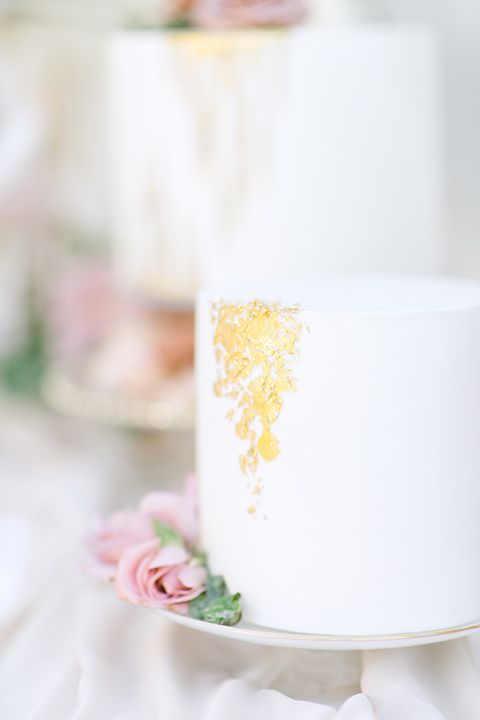 cake with white icing and gold and pink flower decor