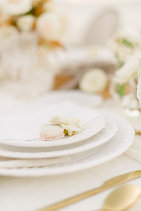 white table with white plates and gold trimmed flatware