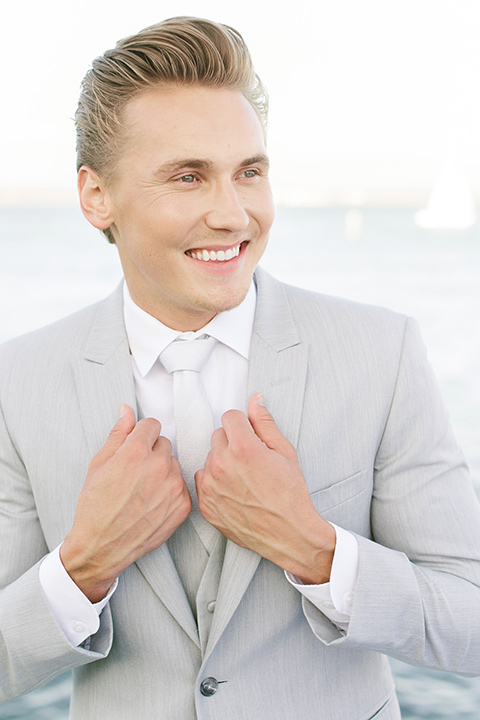 the groom in a light grey suit with a white long tie smiling