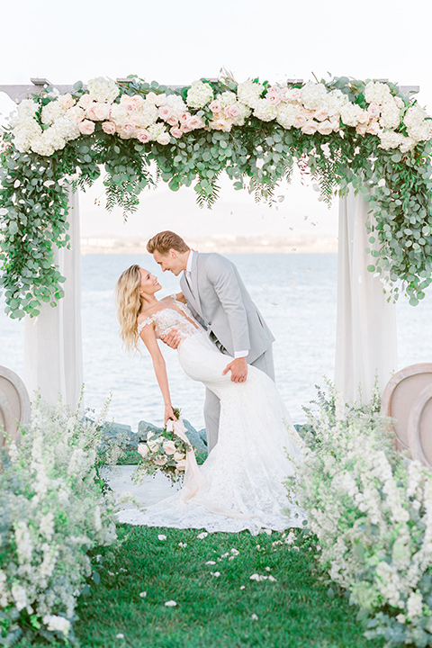 bride in a white formfitting lace gown with an off the shoulder detailing and her hair in loose waves, the groom in a light grey suit with a white long tie kissing at the ceremony