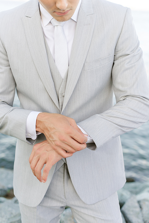 the groom in a light grey suit with a white long tie