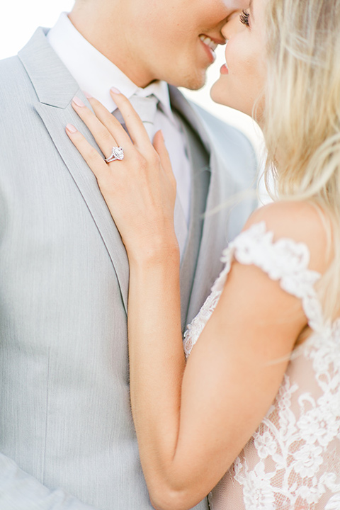 bride in a white formfitting lace gown with an off the shoulder detailing and her hair in loose waves, the groom in a light grey suit with a white long tie close up