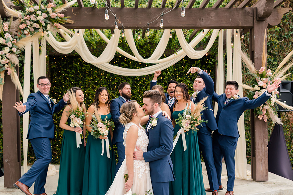 groom in a dark blue suit with a blue bow tie and the bride in a lace gown with a high neckline, and the groomsmen in a blue suit with green bow ties and bridesmaids in green/teal gowns