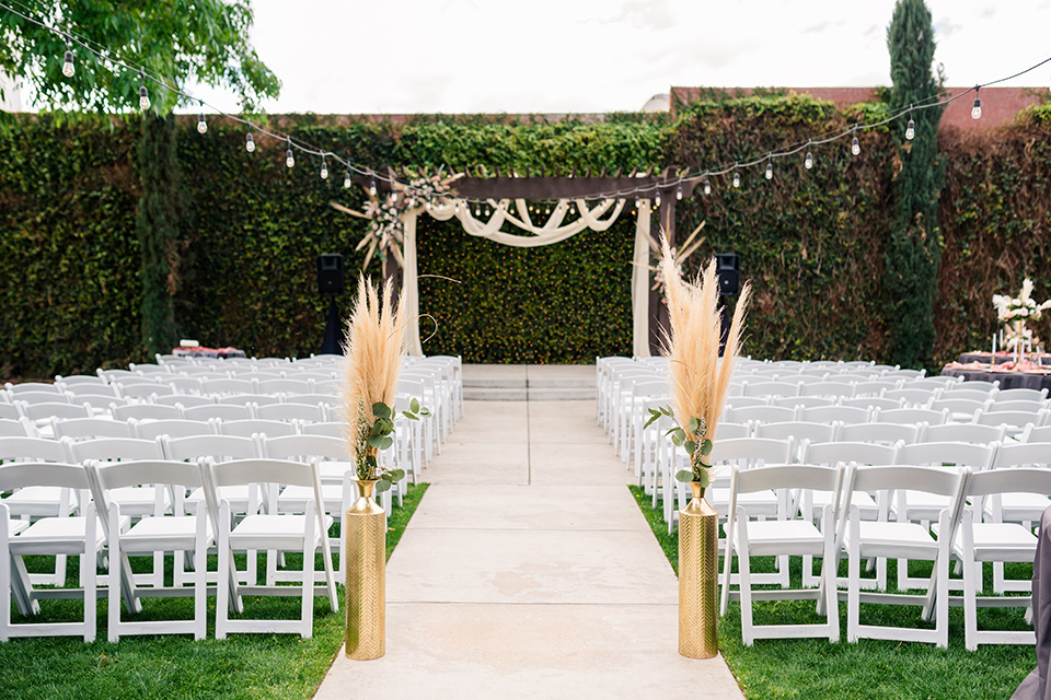 ceremony space with white chairs and pampas grass