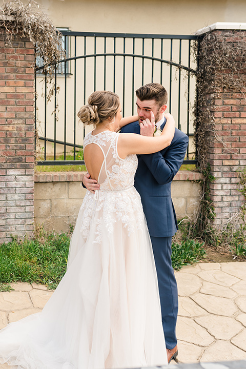 groom in a dark blue suit with a blue bow tie and the bride in a lace gown with a high neckline