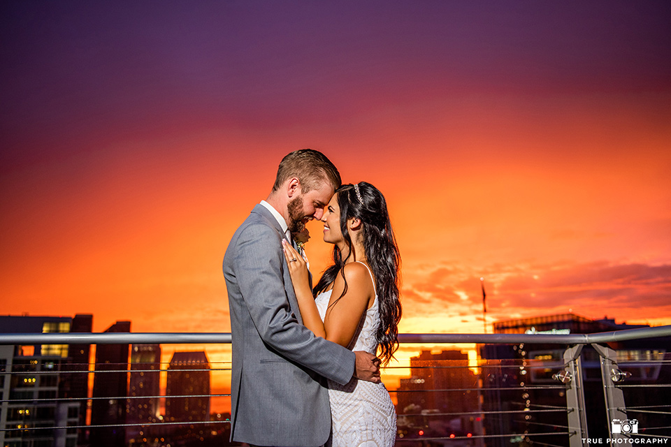 bride in a white formfitting gown with a plunging neckline and a geometric lace design and the groom in a grey suit with a white long tie, at sunset