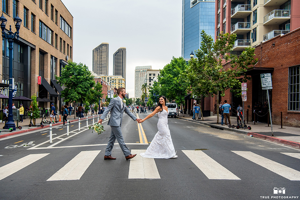 bride in a white formfitting gown with a plunging neckline and a geometric lace design and the groom in a grey suit with a white long tie, crossing the street