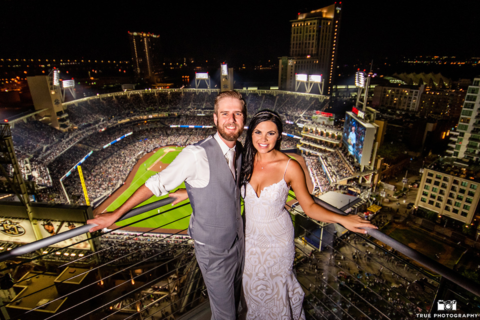 bride in a white formfitting gown with a plunging neckline and a geometric lace design and the groom in a grey suit with a white long tie, in front of petco park in san diego