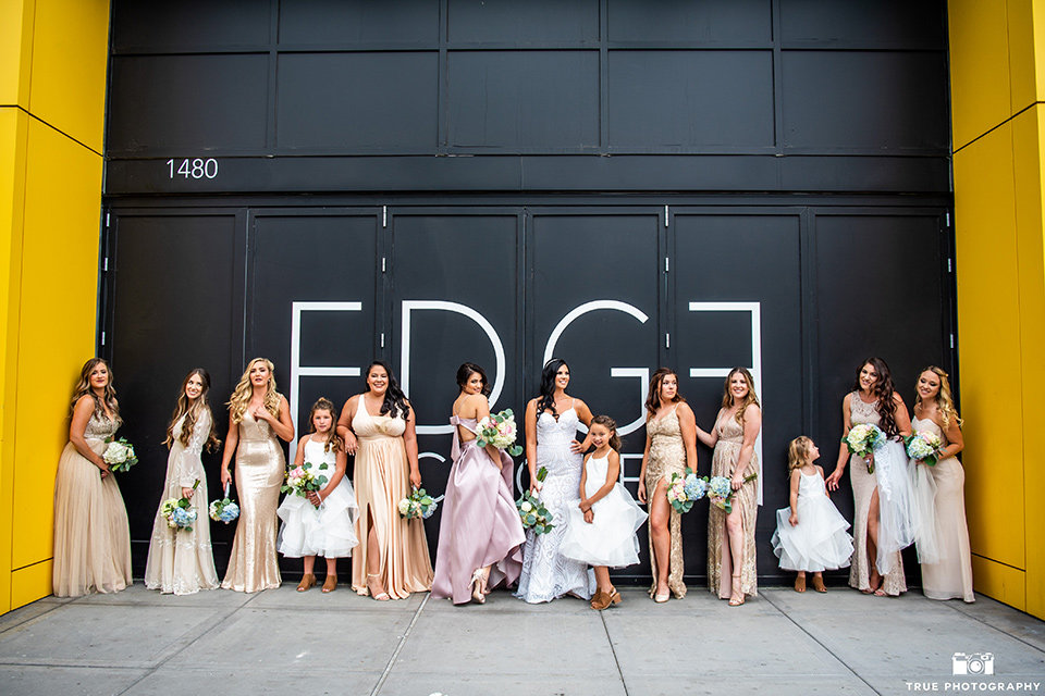 bride in a white formfitting gown with a plunging neckline and a geometric lace design and the groom in a grey suit with a white long tie, the bridesmaids in pink long gowns and the groomsmen in grey suits with light pink long ties