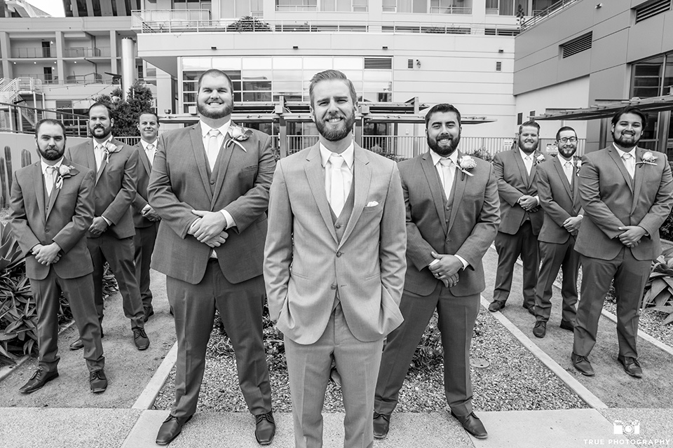 the groom in a grey suit with a white long tie and the groomsmen in a light grey suit and pink long ties