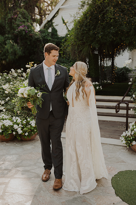 the bride in a flowing white gown with a high lace neckline and a long cathedral veil, the groom in an asphalt grey suit by Michael Kors with a light blue patterned long tie