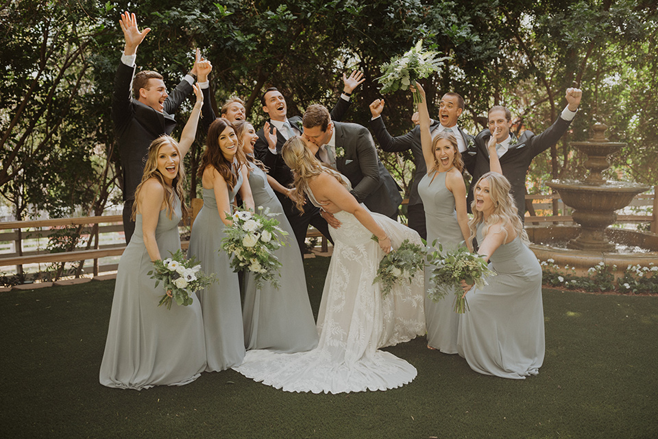 """="""" the bride in a flowing white gown with a high lace neckline and a long cathedral veil, the groom in an asphalt grey suit by Michael Kors with a light blue patterned long tie, the bridesmaids in dusty blue long gowns and the groomsmen in dark grey suits with floral long ties"""