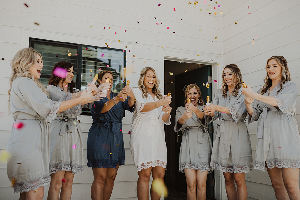 """="""" bride an bridesmaids in robes with champagne"""