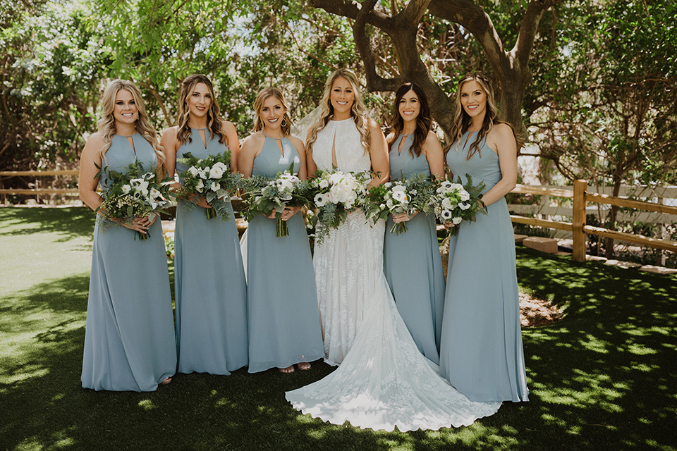 """="""" the bride in a flowing white gown with a high lace neckline and a long cathedral veil, the bridesmaids in dusty blue long gowns"""