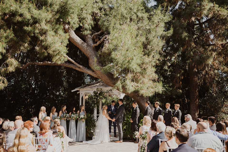 """="""" the bride in a flowing white gown with a high lace neckline and a long cathedral veil, the groom in an asphalt grey suit by Michael Kors with a light blue patterned long tie, the bridesmaids in dusty blue long gowns and the groomsmen in dark grey suits with floral long ties at the ceremony"""