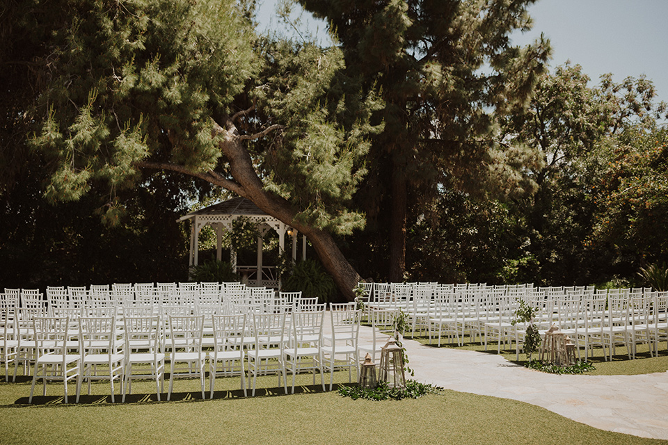 """="""" white chairs for the ceremony over looking tall trees and white flowers"""
