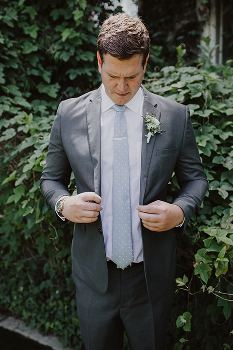 the groom in an asphalt grey suit by Michael Kors with a light blue patterned long tie