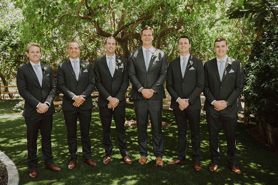 """="""" the groom in an asphalt grey suit by Michael Kors with a light blue patterned long tie and the groomsmen in dark grey suits with floral long ties at the ceremony"""