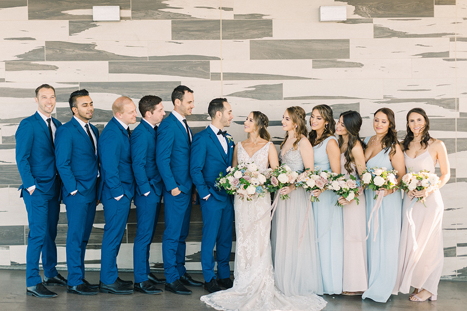 bride in an ivory lace gown with a modern geometric pattern and a v neckline, the groom wore a cobalt blue suit with a black bowtie, the bridesmaids wore different color dresses in pastel tones and the groomsmen in cobalt suits with black long ties