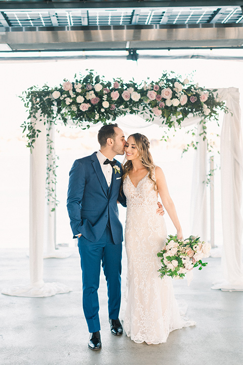 bride in an ivory lace gown with a modern geometric pattern and a v neckline, the groom wore a cobalt blue suit with a black bowtie kissing