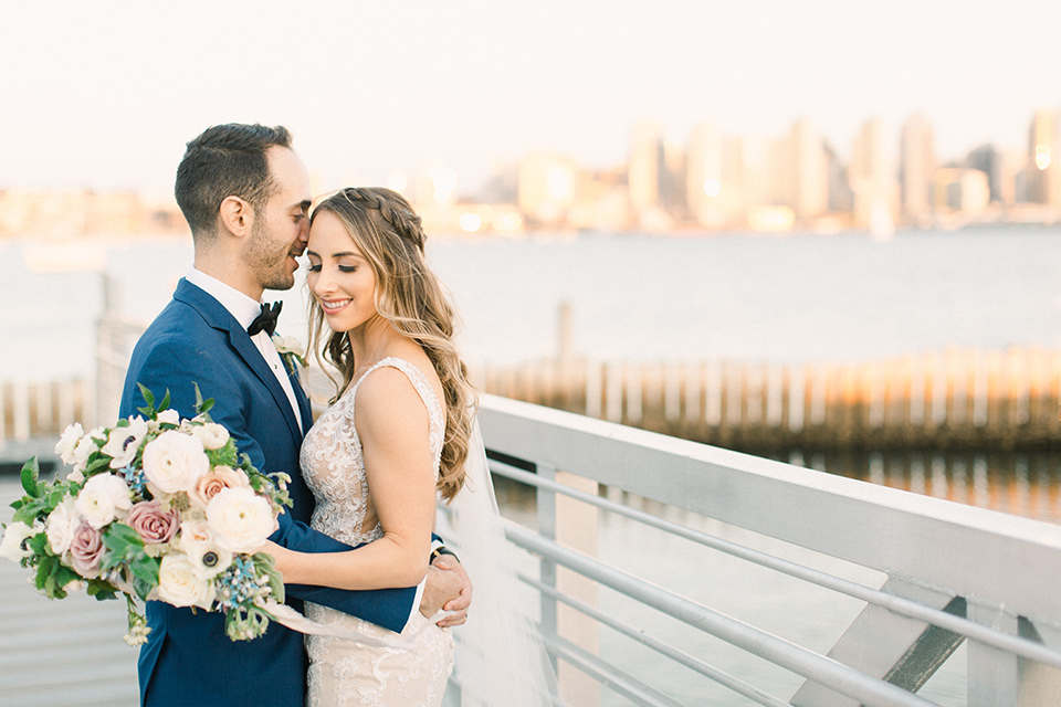 bride in an ivory lace gown with a modern geometric pattern and a v neckline, the groom wore a cobalt blue suit with a black bowtie with skyline and ocean behind them