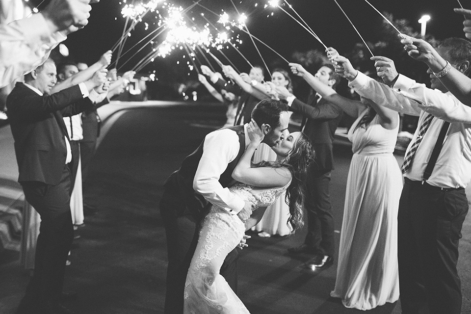 bride in an ivory lace gown with a modern geometric pattern and a v neckline, the groom wore a cobalt blue suit with a black bowtie kissing with sparklers