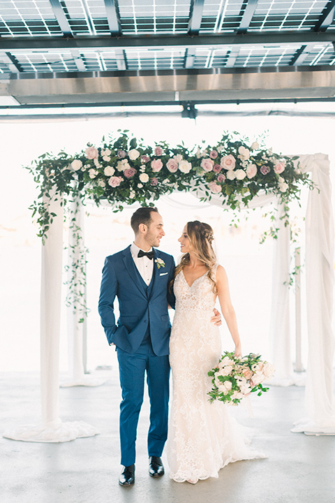 bride in an ivory lace gown with a modern geometric pattern and a v neckline, the groom wore a cobalt blue suit with a black bowtie walking by ceremony space